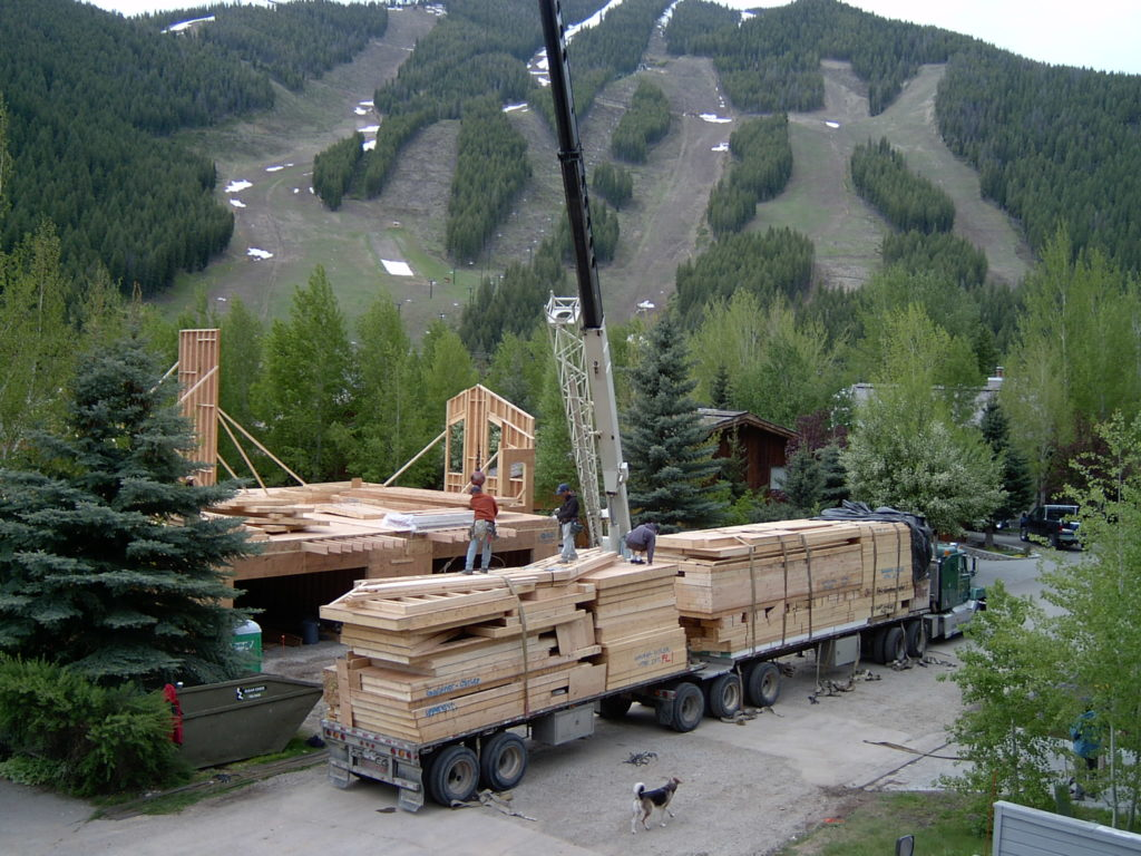 Loaded Pacific Homes truck being craned to a mountainside location